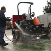 An equipment technician at Pebble Beach Golf Links cleans a Jacobsen mower.