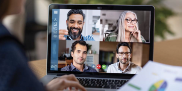 Woman teleconferencing with others via computer.