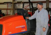 Rich Stuns stands next to a Jacobsen mower he maintains